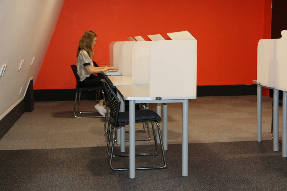 A bright red wall compliments a line of Socrates FOCUS Study Stations.