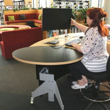 GLO 1600 Desk with its open and inviting form is positioned alongside an area where customers can sit and use devices.