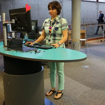 Mona Vale Library staff member working at a comfortable standing height on YAKETY YAK Classic Oval's ergonomic worktop.